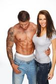 Young woman embracing man with naked muscular torso — Foto Stock