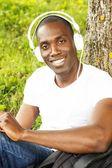 Afryki amerykański młodzieńca w białej koszuli słucha muzyki w parku — Zdjęcie stockowe