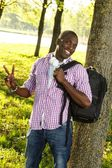 Positive young african american with backpack and earphones in a park — Stock Photo