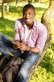 Young smiling african american sitting on a tree in park with mobile phone — Stock Photo
