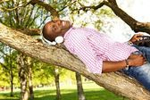 Young african american lying on a tree branch in a park and listens to music — Stock Photo
