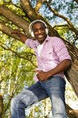 Positive young african american man listens music in a park — Stock Photo