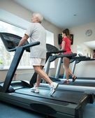 Senior man and young woman walking on a treadmill — Stock Photo