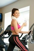Young woman doing exercise in fitness club on training machine — Stock Photo