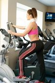 Young woman doing exercise in fitness club on training machine — ストック写真