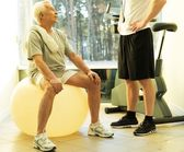 Personal trainer explains to a senior man how to do exercise on a fitness ball — Stock Photo
