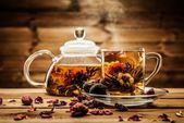 Teapot and glass cup with blooming tea flower inside against wooden background — Stock Photo