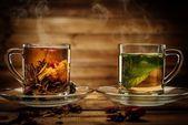 Glas tassen mit tee aus holz hintergrund — Stockfoto