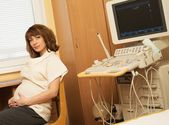 Young pregnant woman in ultrasound examination cabinet at hospital — Stock Photo