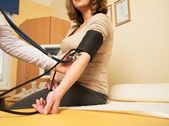 Young pregnant woman in ultrasound examination measuring blood pressure — Stock Photo