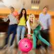 Group of four young smiling people playing bowling — Stock Photo #40061083