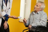 Nurse woman giving client card to senior man in wheelchair — Stock Photo