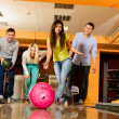 Group of four young smiling people playing bowling — Stockfoto #40275437