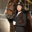 Beautiful girl with her horse in a stall — Stock Photo #40275567
