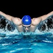 Muscular young man in blue cap in swimming pool — Stock Photo