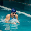 Young woman in blue cap and swimming suit in pool — Stock Photo #40276475