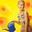 Beautiful young cheerful blond woman in colorful dress among big yellow flowers with watering can — Stock Photo #40276891
