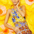 Beautiful young blond woman in colourful dress lying among big yellow flowers — Stock Photo #40276897