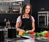 Cheerful young woman in apron on modern kitchen cutting vegetables — Foto Stock