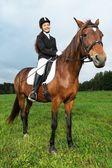Веселая молодая женщина, избавление лошади в поле — Стоковое фото