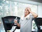 Tired senior man on a treadmill with towel and bottle of water — Stock Photo