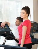 Trainer explains to a young woman how to use treadmill in fitness club — Stock Photo