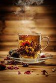 Taza de cristal con flor de té contra fondo de madera — Foto de Stock