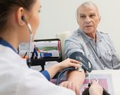 Senior man measuring blood pressure at doctor's office — Foto Stock