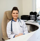 Cheerful young doctor woman in her office behind table — Стоковое фото