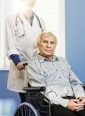 Cheerful young nurse woman with senior man in wheelchair — Stock Photo
