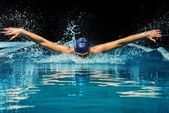 Young woman in blue cap and swimming suit in pool — Stock Photo
