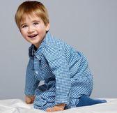 Little boy wearing blue pyjamas in bed — Stock Photo