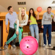 Group of four young smiling people playing bowling — Stock Photo #40586183