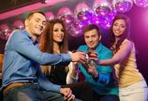 Group of cheerful young friends sitting with drinks at night club — Stock Photo