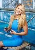 Jovem mulher loira em fato de banho sentado em um banco perto da piscina — Fotografia Stock