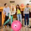 Group of four young smiling people playing bowling — Stock Photo #40692631
