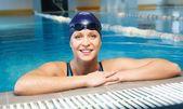 Yüzme havuzunda mavi yüzme takım elbise ve şapka giyen genç kadın — Stok fotoğraf