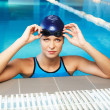 Young woman wearing blue swimming suit and hat in swimming pool — Stok fotoğraf