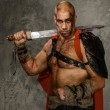 Stock Photo: Wounded gladiator with sword covered in blood isolated on grey