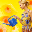 Beautiful young cheerful blond woman in colorful dress among big yellow flowers with watering can — Stock Photo #40761945