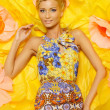 Beautiful young blond woman in colourful dress lying among big yellow flowers — Stock Photo #40761971