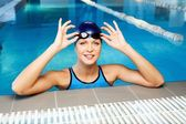 Young woman wearing blue swimming suit and hat in swimming pool — Stock Photo