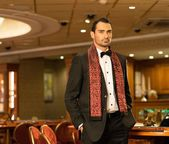 Handsome brunette wearing suit and scarf in luxury interior — Stock Photo