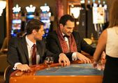Two young well-dressed men behind gambling table in a casino — Stock Photo