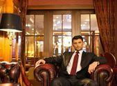 Confident handsome brunette sitting in luxury interior — Stock Photo