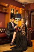 Elegant couple in formal dress in luxury cabinet interior — Stock Photo