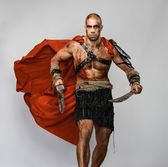Wounded gladiator with two swords covered in blood isolated on grey — Stock Photo