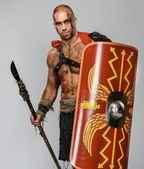 Wounded gladiator with spear and shield — Stock Photo
