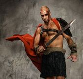 Wounded gladiator with sword covered in blood isolated on grey — Stock Photo