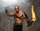Wounded gladiator holding torch and sword covered in blood — Stock Photo